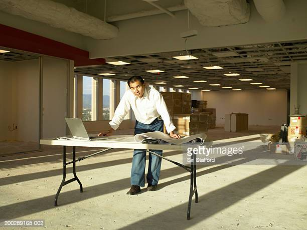 Businessman standing at table with laptop in empty office