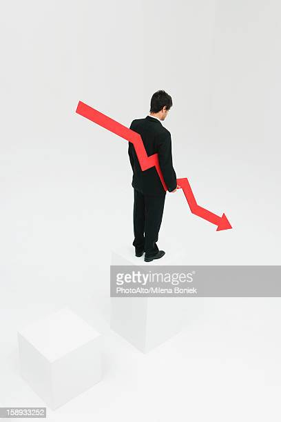 Businessman standing at top of steps holding arrow pointed downward