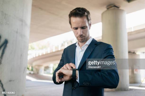 businessman standing at underpass using smartwatch - wrist watch stock pictures, royalty-free photos & images