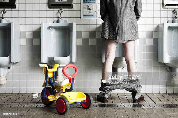Businessman standing at urinal with his tricycle