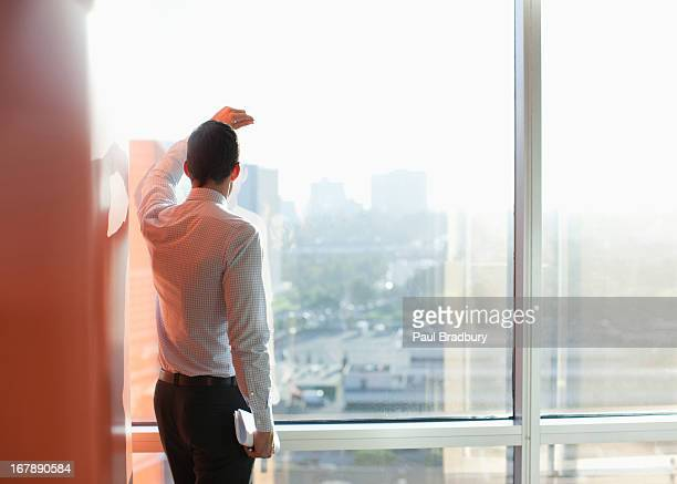 Businessman standing at window in office