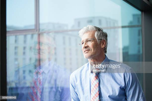 Businessman standing at window looking at distance