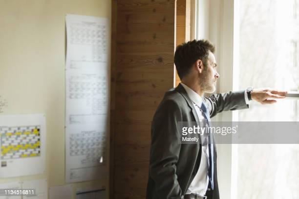 businessman standing at window - waiting stock-fotos und bilder