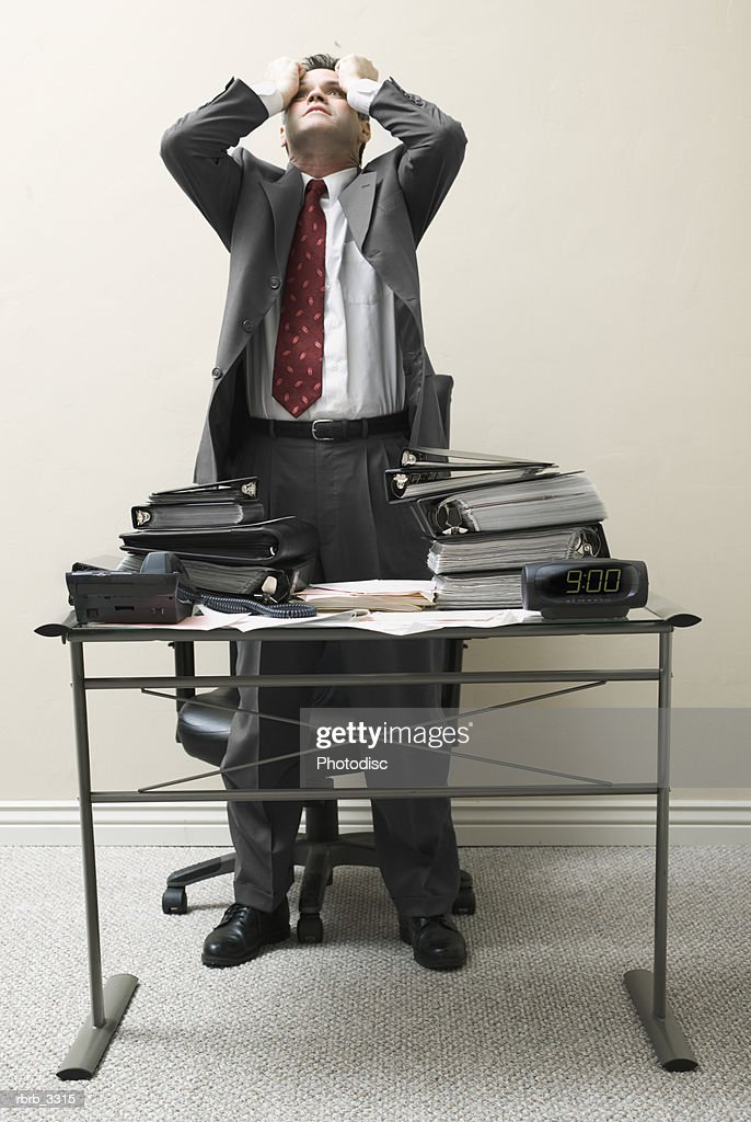 Businessman standing behind a desk with his hands on his head : Foto de stock