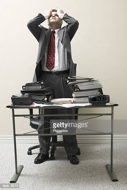 Businessman standing behind a desk with his hands on his head