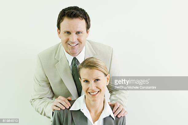 Businessman standing behind female associate with his hands on her shoulders, both smiling at camera