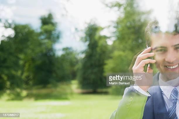 Geschäftsmann, stehen hinter Glas redet mit Handy