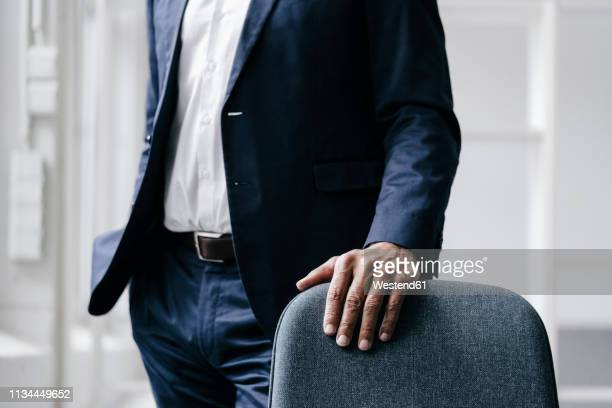 businessman standing behind office chair, partial view - formal businesswear stock pictures, royalty-free photos & images