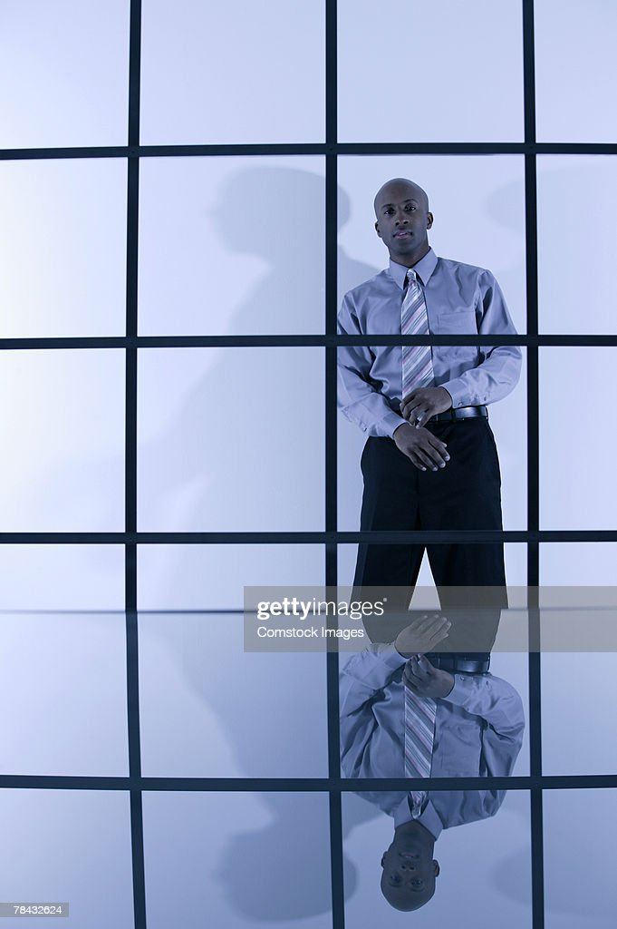 Businessman standing behind window with bars : Stock Photo