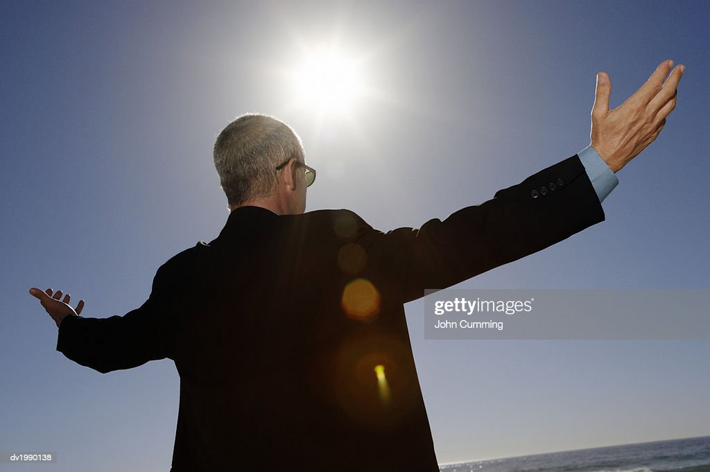 Businessman Standing Below Bright Sunlight With His Arms Out : Stock Photo