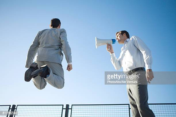 Businessman standing beside colleague, shouting into megaphone, colleague jumping in air, low angle view