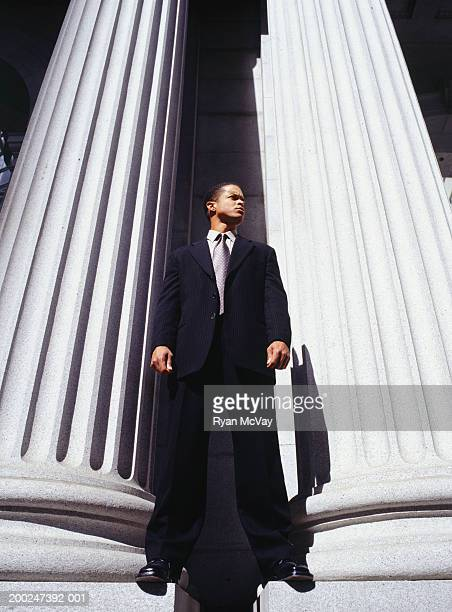 businessman standing between columns - mid adult men stock pictures, royalty-free photos & images