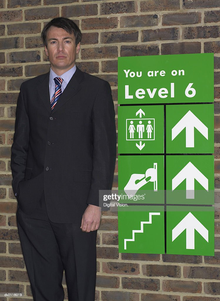 Businessman Standing by a Car Park Sign : Stock Photo