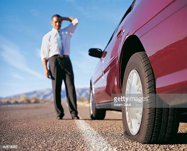 businessman standing by a car with a punctured tyre - flat tire stock pictures, royalty-free photos & images