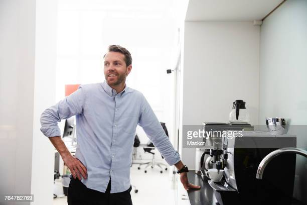 Businessman standing by coffee maker at counter in creative office