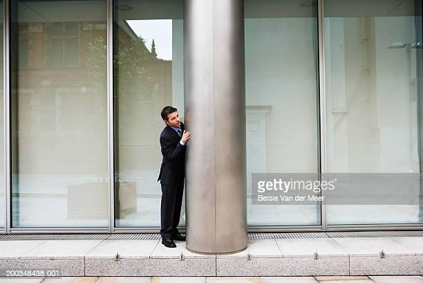 businessman standing by column on exterior of building - チラッと覗く ストックフォトと画像