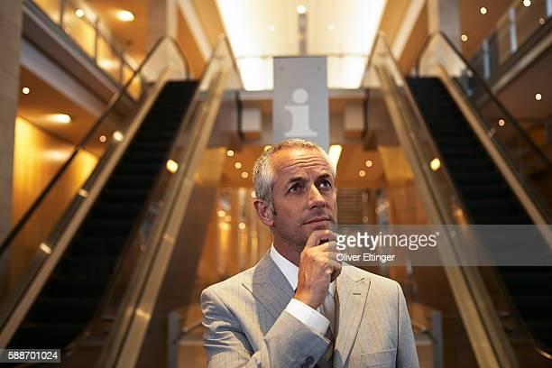businessman standing by escalators - oliver eltinger stock-fotos und bilder