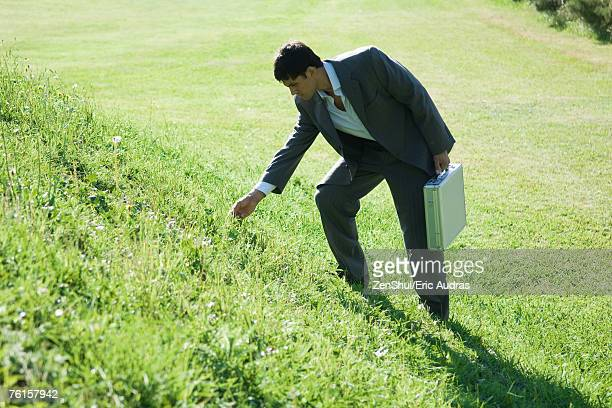Businessman standing by grassy hill, bending down to touch grass