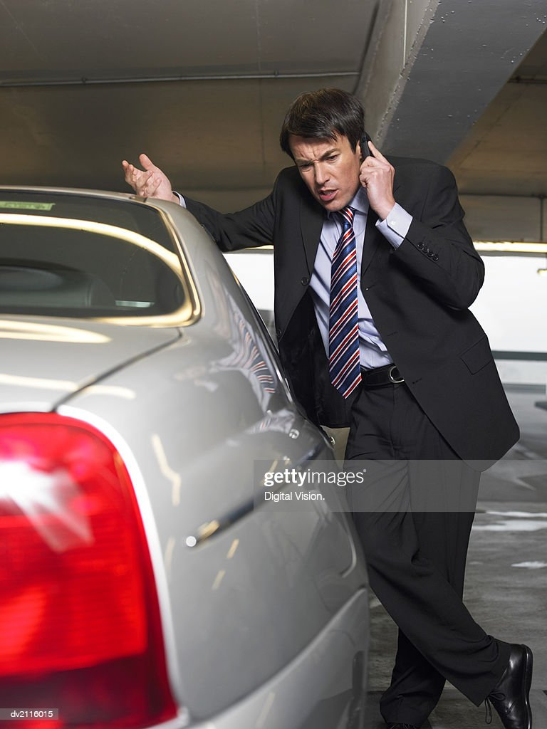 Businessman Standing by His Car and Using His Mobile Phone : Stock Photo