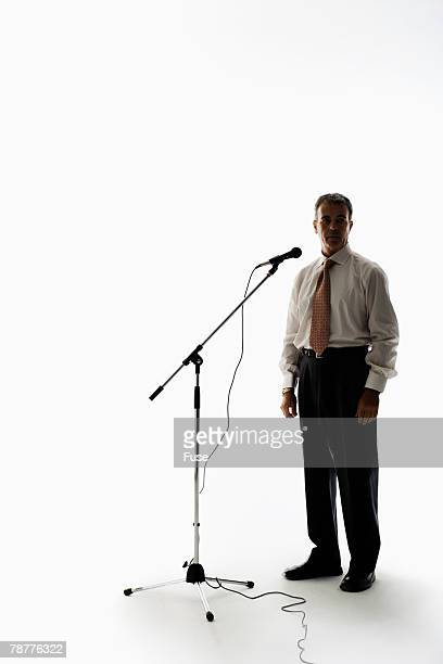 Businessman Standing by Microphone
