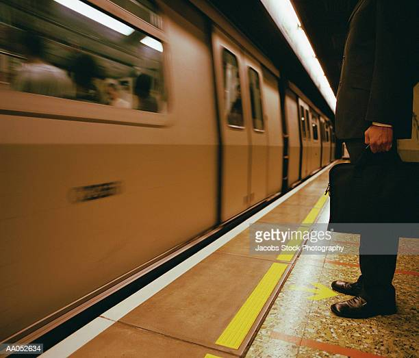 Businessman standing by moving subway, high section (blurred motion)