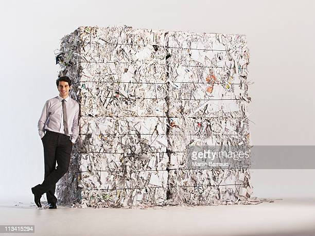 Businessman standing by stack of paper bales