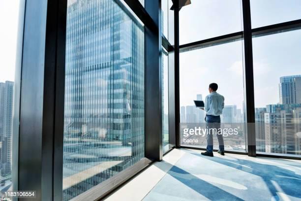 empresario de pie junto a la ventana y usando computadora portátil - top fotografías e imágenes de stock