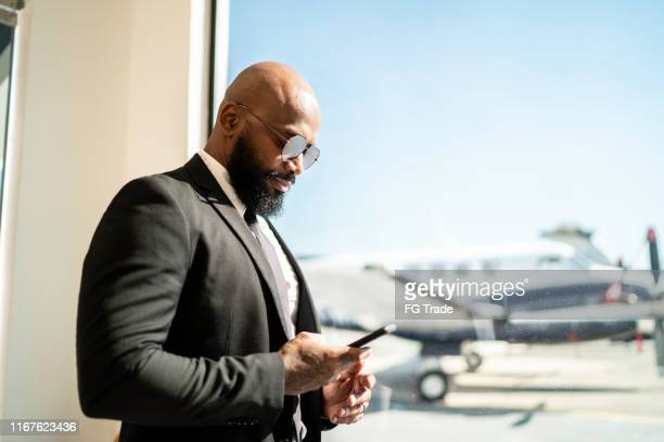 businessman standing by the window and using smartphone in airport - best sunglasses for bald men stock pictures, royalty-free photos & images