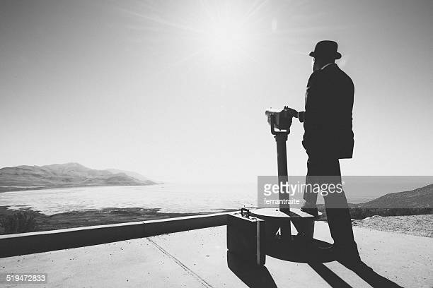 Businessman standing by viewpoint telescope