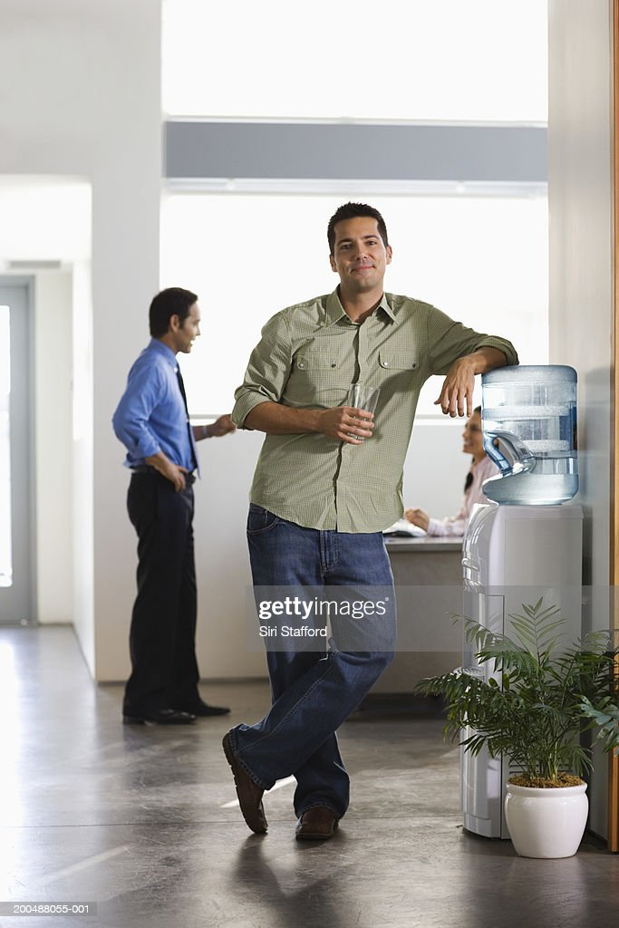 Businessman Standing By Water Cooler In Office Stock Photo | Getty ...