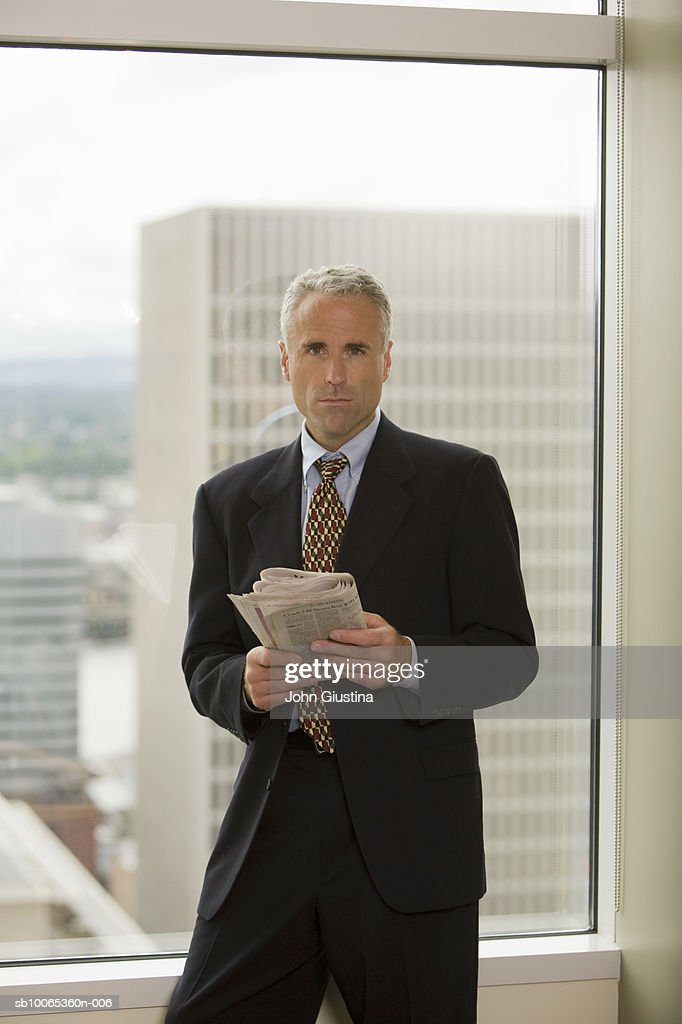 Businessman standing by window holding newspaper, portrait : Foto stock