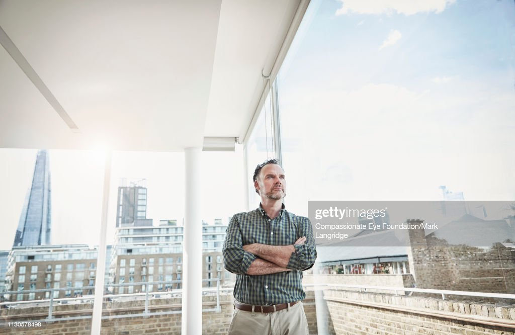 Businessman standing by window in modern office : Stock Photo