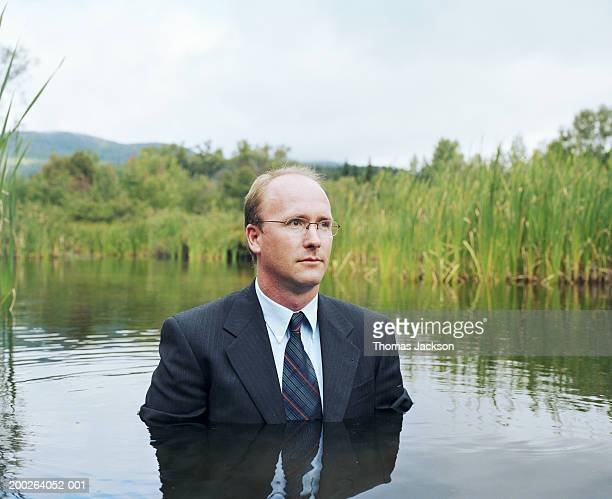 businessman standing chest deep in water - receding hairline stock pictures, royalty-free photos & images