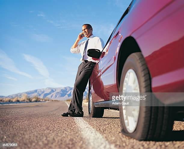 Businessman Standing Holding a Mobile Phone Next to His Car With a Punctured Tyre