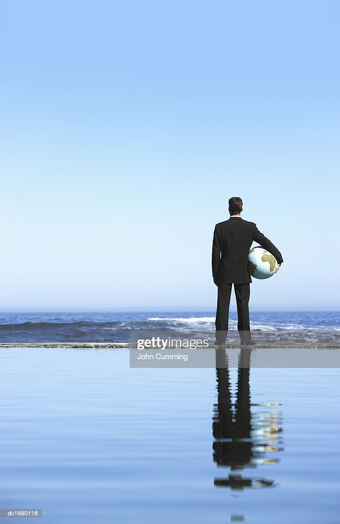 Businessman Standing Holding a Sphere and Looking at the Sea : Stock Photo
