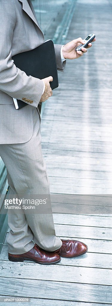 Businessman standing, holding file and dialing cell phone, chest down, panoramic : Stockfoto