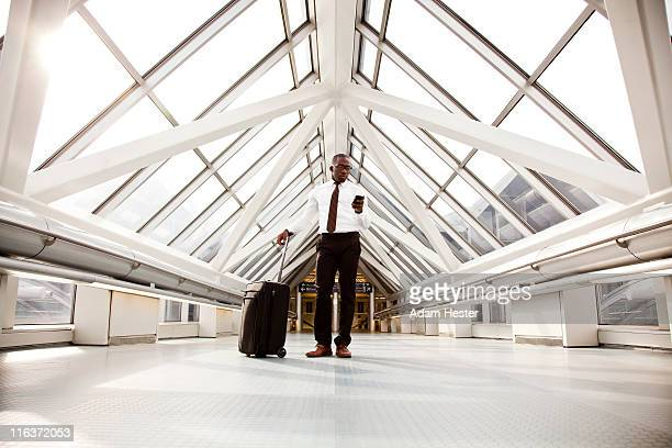 A businessman standing in a airport with luggage.