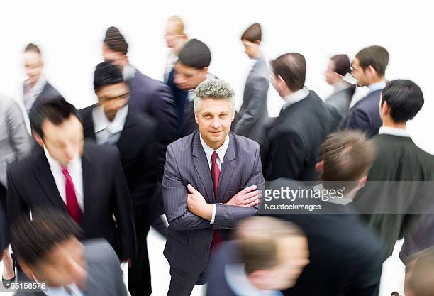Businessman Standing in a Crowd of Moving People