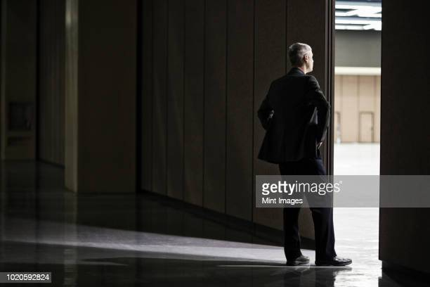 businessman standing in a doorway between rooms in a convention centre arena. - doorway stock pictures, royalty-free photos & images