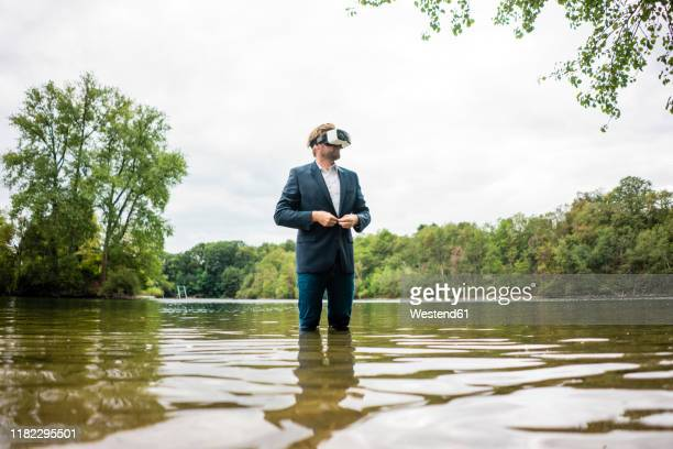 businessman standing in a lake wearing vr glasses - wading stock pictures, royalty-free photos & images