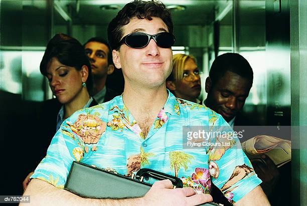 businessman standing in a lift wearing sunglasses and an unconventional shirt - hawaiian shirt stock photos and pictures