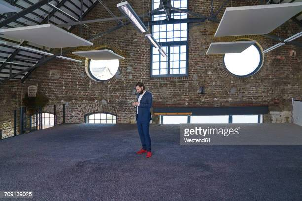 businessman standing in a loft using cell phone - ziegelbau stock-fotos und bilder