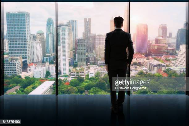 businessman standing  in a office and looking at city - 東南アジア ストックフォトと画像