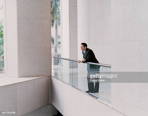 Businessman Standing in An office Building Thinking