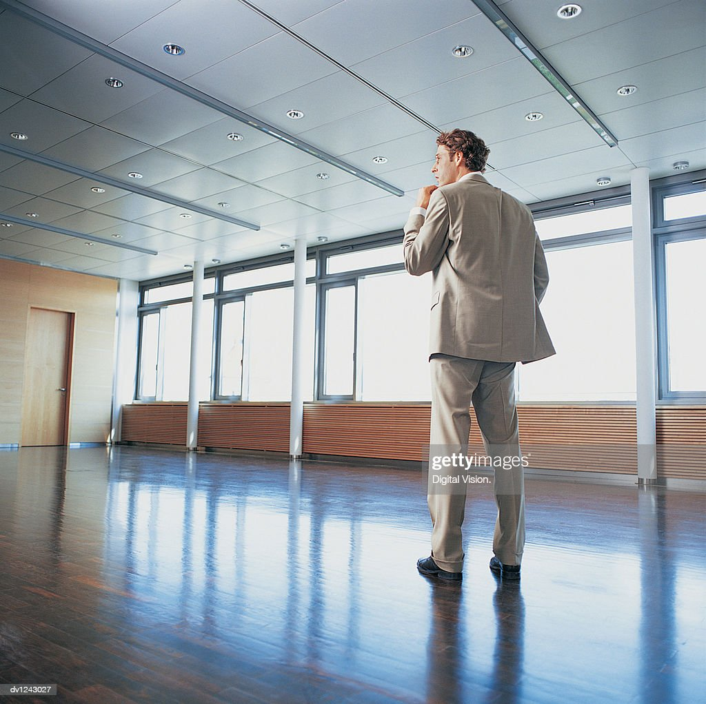 Businessman Standing in an Office With His Hand on  His Chin : Stock Photo