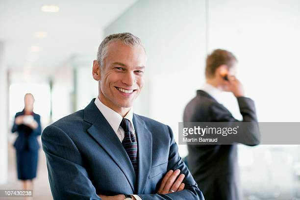 businessman standing in busy office - full suit stock pictures, royalty-free photos & images