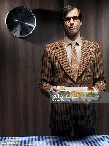 Businessman standing in canteen holding lunch tray, portrait