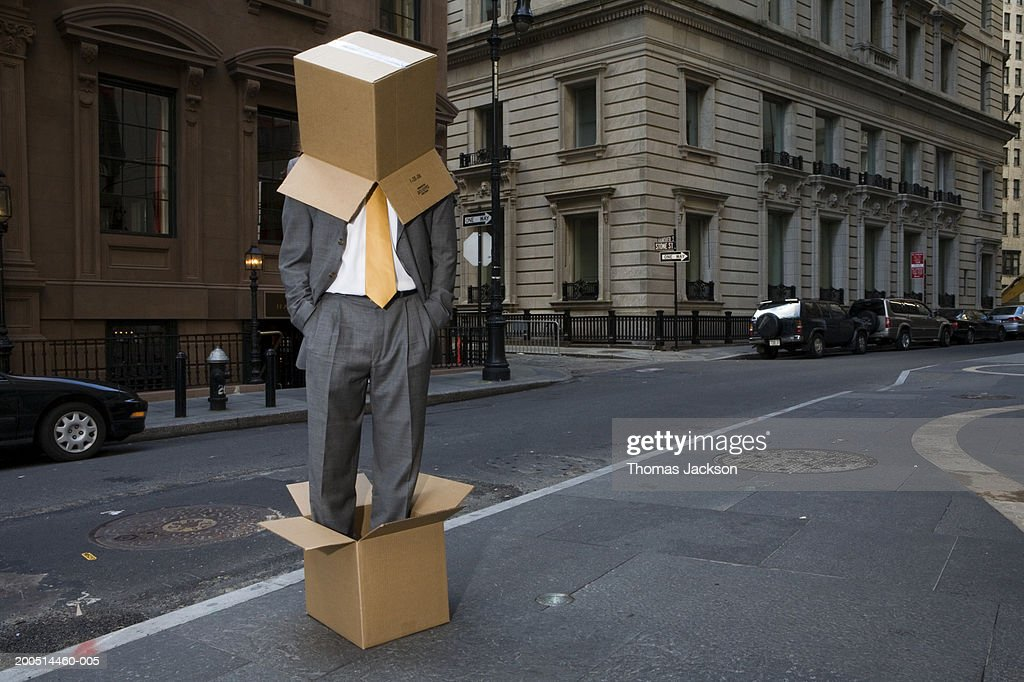 Businessman standing in cardboard box and wearing one on head on city street : Stock Photo