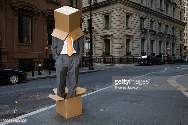 Businessman standing in cardboard box and wearing one on head on city street