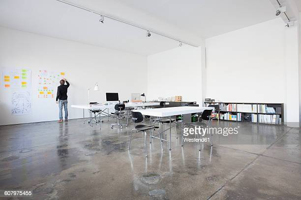 businessman standing in conference room at wall - distant stock photos and pictures